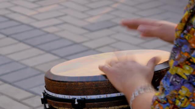 vidéos et rushes de homme jouant le tambour ethnique sur la rue - instrument à percussion