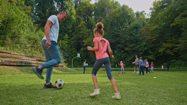 man spelar fotboll med sin dotter i naturen - enbarnsfamilj bildbanksvideor och videomaterial från bakom kulisserna