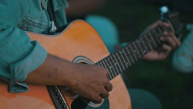 vídeos de stock, filmes e b-roll de homem tocando guitarra closeup, ao ar livre - música acústica