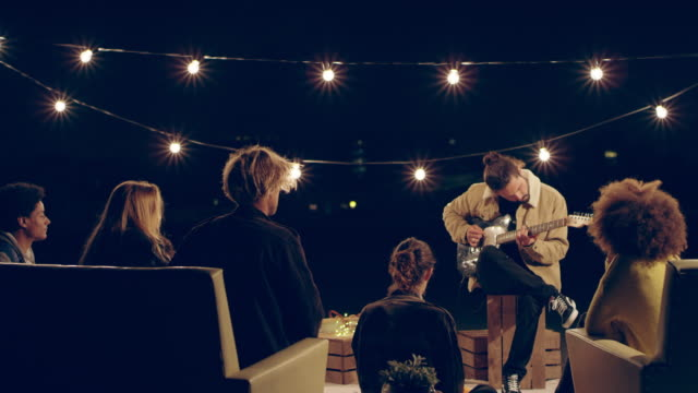 man playing guitar for friends in rooftop party - terrazza video stock e b–roll