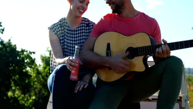 Man playing guitar for woman 4k video