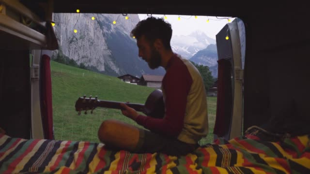 Man playing guitar  in camper van Young Caucasian man playing guitar  in camper van  in Swiss Alps rv interior stock videos & royalty-free footage