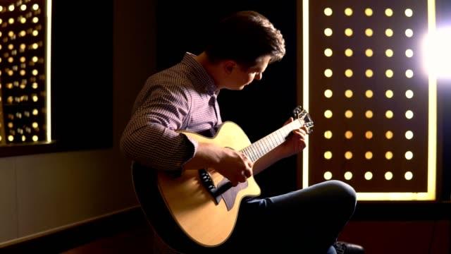 vidéos et rushes de homme jouant la guitare dans le studio - compositeur
