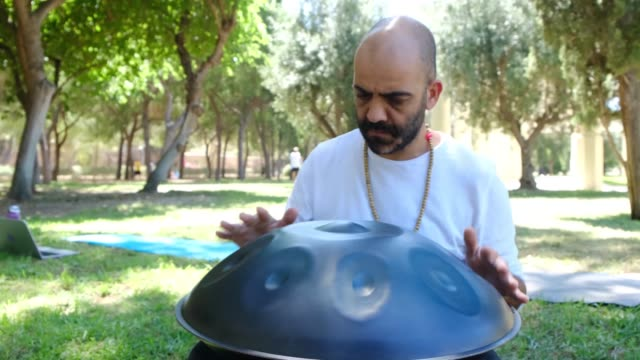 Man playing handpan drum in an outdoor park