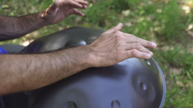 Man playing handpan Musician hands playing handpan drum in nature scene. hanging stock videos & royalty-free footage