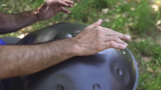 stockvideo's en b-roll-footage met man spelen handpan - hangen