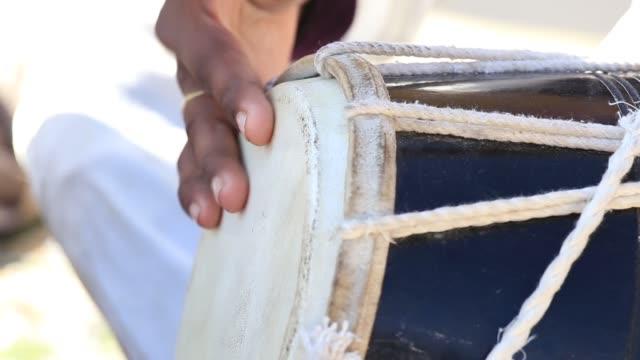 vídeos de stock e filmes b-roll de man playing on a bongo drum in jaisalmer fort, rajasthan, india - bateria instrumento de percussão