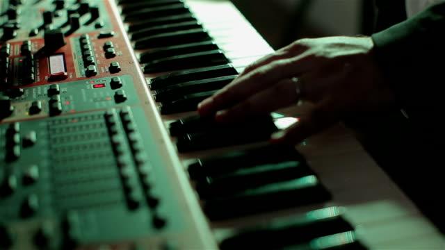 vídeos de stock, filmes e b-roll de homem jogando no sintetizador em uma rocha concert.hands de um homem tocando um sintetizador na luz - músico pop