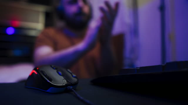Man Playing online multiplayer game on his room and celebrating his friends for winning the game video
