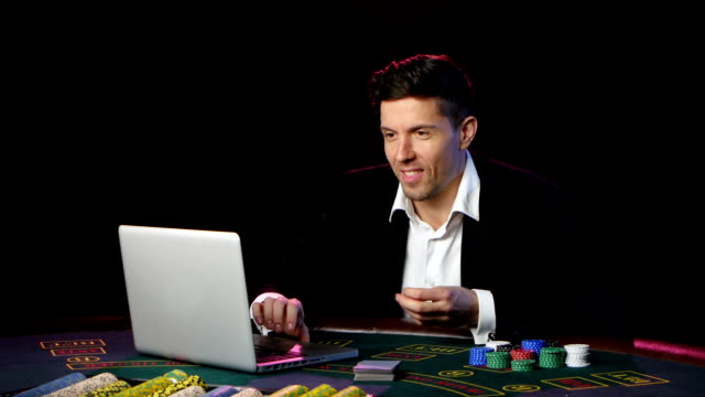 Man playing online poker at a table. Close up video