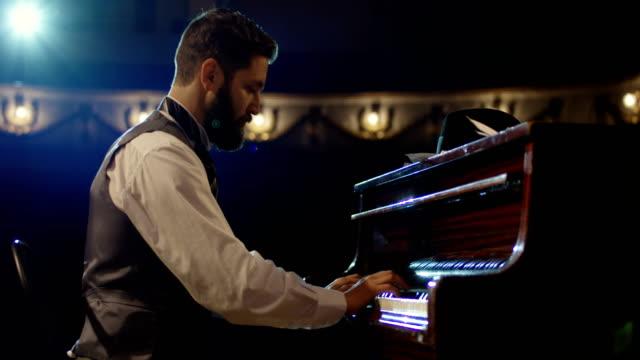 vídeos de stock e filmes b-roll de man playing piano on the stage - piano