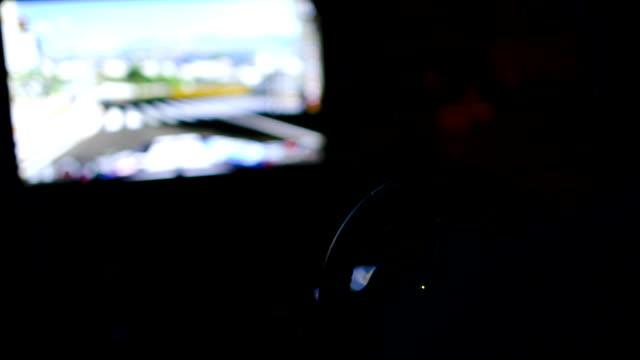 człowiek gra wyścigi gra z kierownicą w ciemności. - ster fragment pojazdu filmów i materiałów b-roll