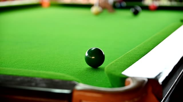 Man playing snooker with aiming for green ball on bar
