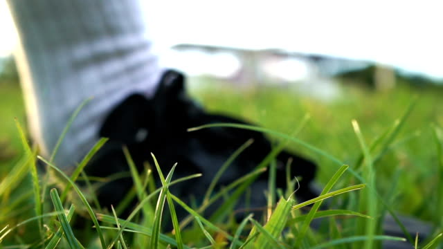 CU: A man playing soccer on a grassy field. - Slow Motion