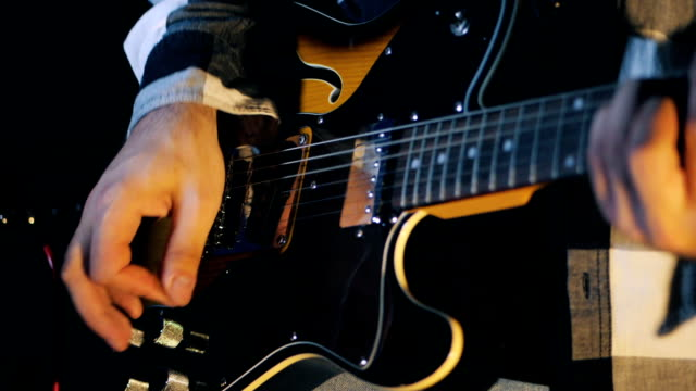 man playing the electric guitar at the concert. Close up view of guitarist plays electro guitar in dark room. Slowmotion video