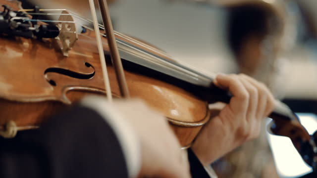 Man playing violin at a concert Man playing violin in symphony orchestra. Bangkok, Thailand. musical theater stock videos & royalty-free footage