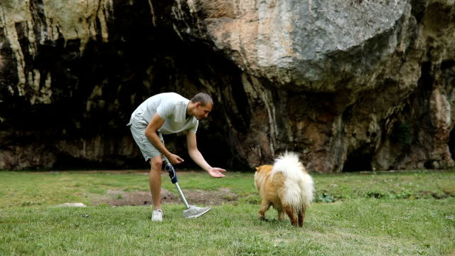 Man playing with pet in nature