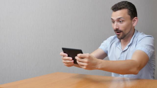 stockvideo's en b-roll-footage met man speelt een spel op de tablet pc - bewondering