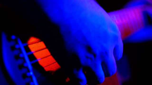 A man plays an acoustic guitar near a microphone during a concert on stage with neon lighting video