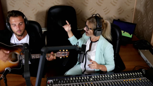 man plays guitar live into microphone near woman in headphones beside console video