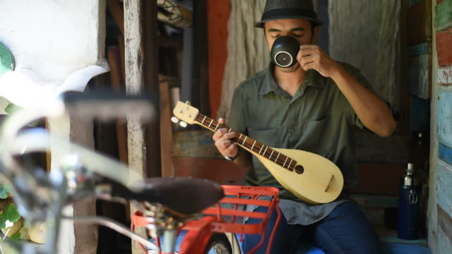 A man plays mandolin and drinks coffee at the vintage house. video