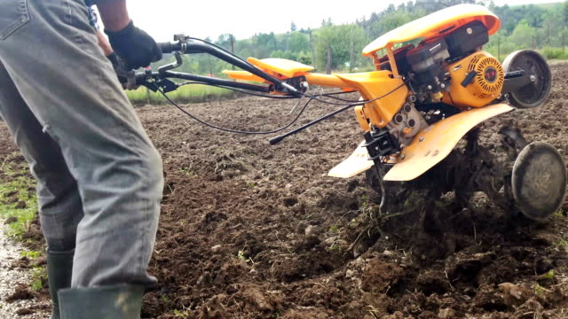 Man plowing field with cultivator, garden preparation Man plowing field with cultivator, garden preparation.mov harrow agricultural equipment stock videos & royalty-free footage
