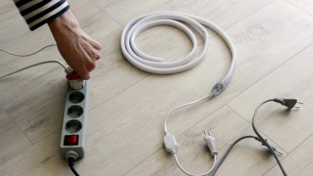 vidéos et rushes de man plug in socket electrical surge protector and turn on the led strip. - rallonge électrique