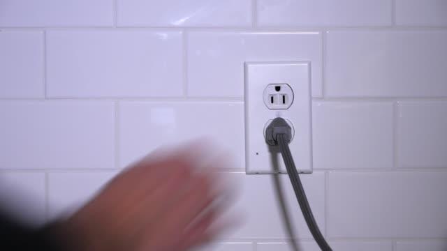 vidéos et rushes de homme branche câble électrique dans la prise de cuisine - vidéos de rallonge électrique