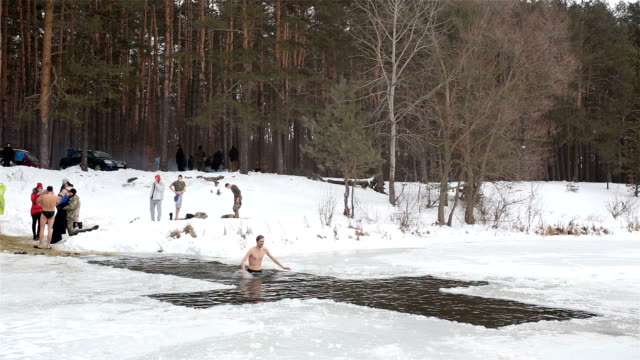 man plunges in cold water during the celebration of epiphany. - baptism stock videos and b-roll footage