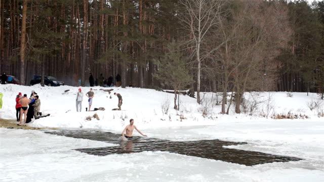 vidéos et rushes de l'homme plonge dans l'eau froide lors de la célébration de l'épiphanie. - baptême
