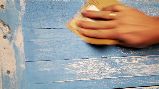 A man polishes wooden board with a piece of sandpaper video