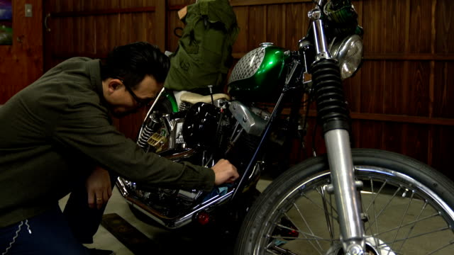 Man polishing and maintaining his custom motorcycle in his garage video