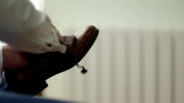 slo mo primo piano di uomo lucidare le scarpe in pelle marrone - lucidare video stock e b–roll