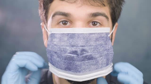Man portrait Wearing Hygiene protection Mask and gloves prevention against Virus Doctor put on surgical protection Mask and gloves prevention against Influenza. health care Corona Virus  prevention icon glove stock videos & royalty-free footage