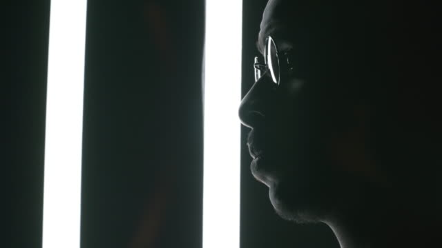 Man Posing in Dark Studio with Fluorescent Lamps Side portrait with close up of face of black man in round glasses and hat standing in dark studio with fluorescent tubes swinging behind him low lighting stock videos & royalty-free footage