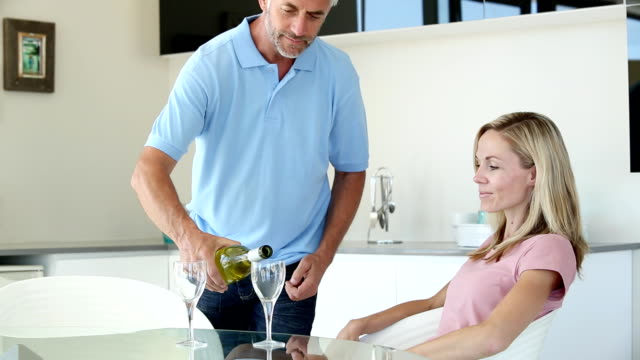 Man pouring a glass of wine for partner Man pretending to be waiter pouring a glass of wine for partner at the kitchen table wait staff stock videos & royalty-free footage