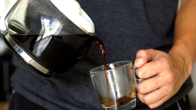 A man pouring a mug of hot coffee from a glass pot in the morning at home. video