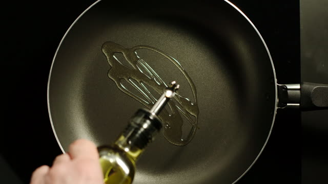 Man pouring cooking oil on the frying pan - Top View Man pouring cooking oil on the frying pan - Top View cooking pan stock videos & royalty-free footage
