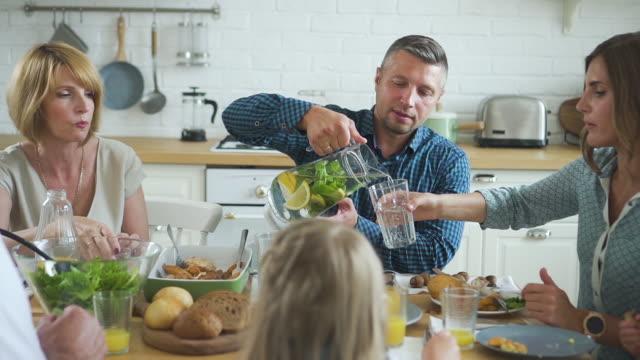 vídeos de stock e filmes b-roll de man pouring lemonade and juice in drink at family gathering dinner - limonada tradicional