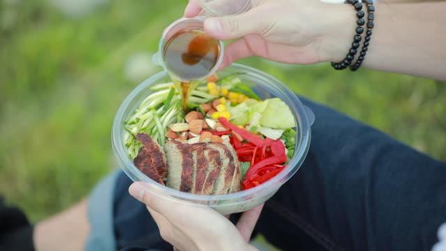 vídeos de stock e filmes b-roll de man pouring sauce into salad - saladeira