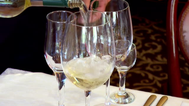 A man pours a glass of white wine A man pours a glass of white wine Close-up kitchen utensil stock videos & royalty-free footage