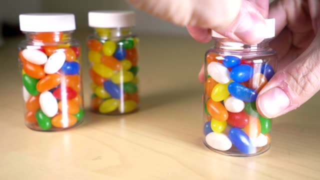 A man pours out multicolored pills into her hand A man pours out multicolored pills into her hand. Suitable for automedication, India National Anti Drug Addiction Day, National Doctors' Day or World Health Day world health day stock videos & royalty-free footage