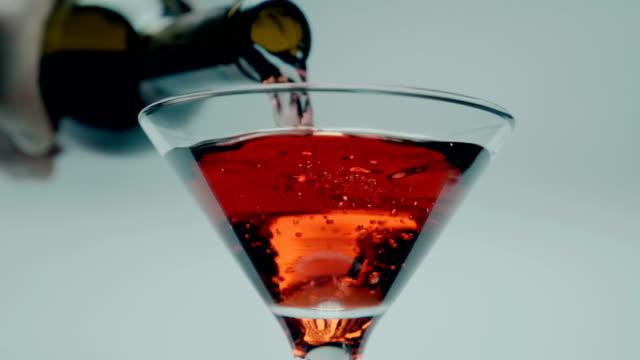 ein mann gießt roten martini (wein, alkoholisches getränk) aus einer flasche in ein glas - cabernet sauvignon traube stock-videos und b-roll-filmmaterial