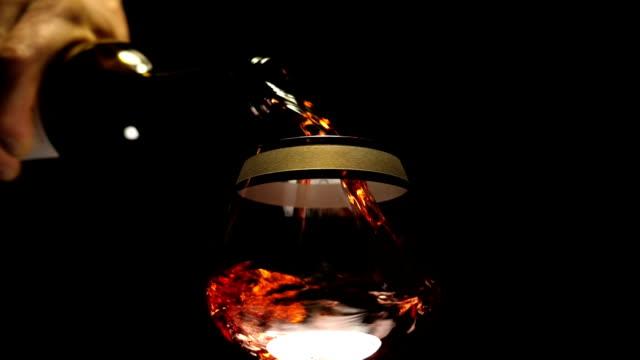 ein mann gießt rotwein aus einer flasche in einen glaskelch auf schwarzem hintergrund - cabernet sauvignon traube stock-videos und b-roll-filmmaterial