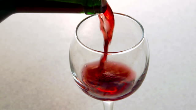 Man pours red wine into glass standing on table in kitchen video