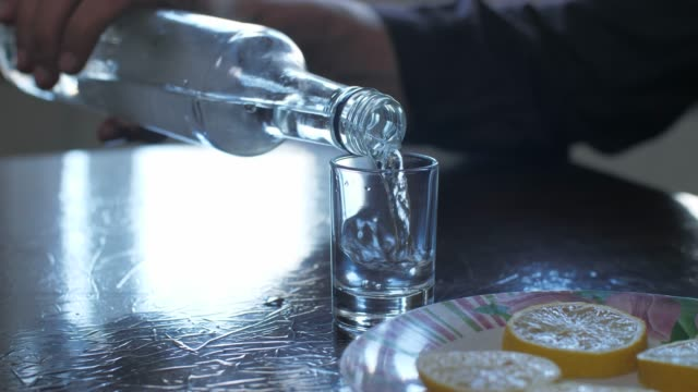 man pours vodka into a glass - vodka video stock e b–roll