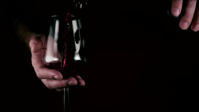 A man pours wine into a glass on black background. Slow motion