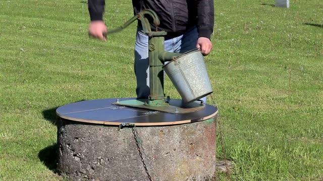 man powered water pump at the well - värmepump bildbanksvideor och videomaterial från bakom kulisserna