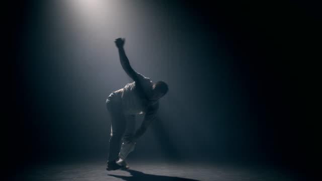 vídeos y material grabado en eventos de stock de hombre practicando capoeira en el cuarto oscuro - artes marciales