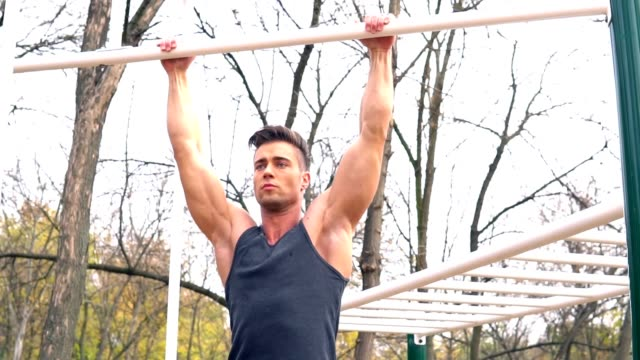 Man practicing chin-ups in the park video
